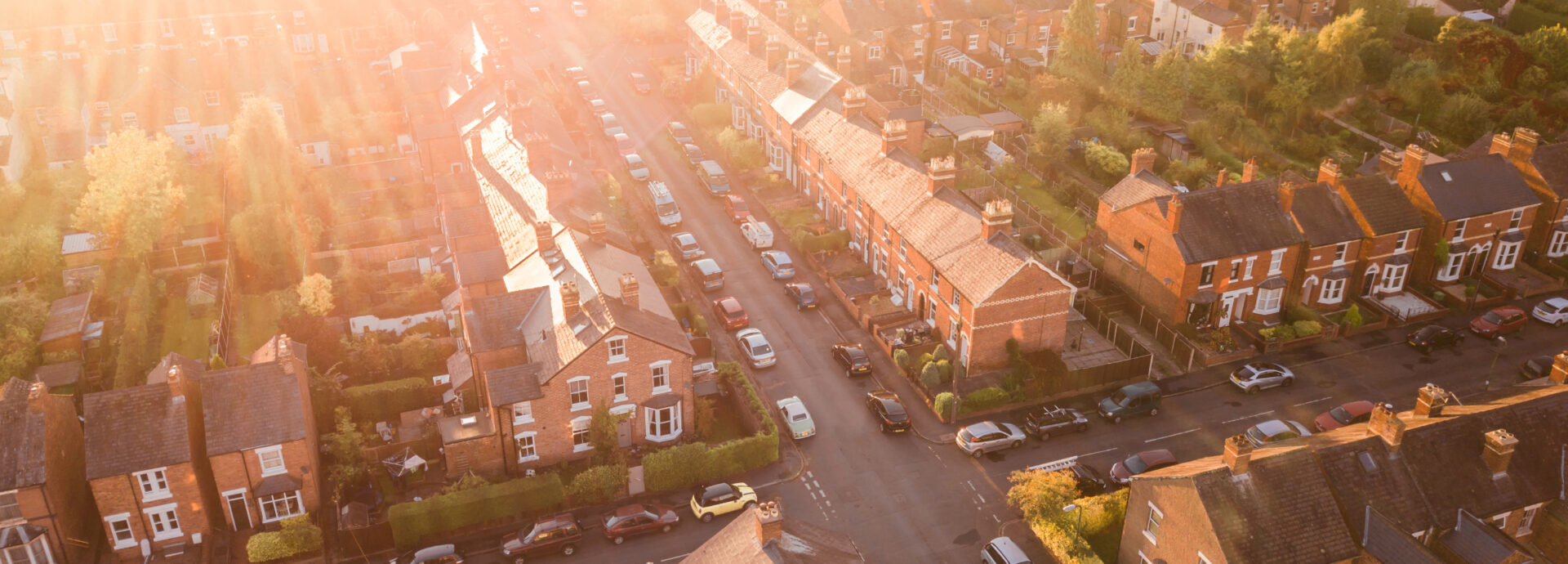 Aerial view of the sun setting over a cross roads in a traditional UK suburb.